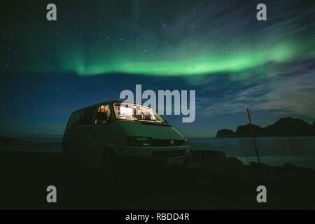 Northern lights above the VW van. MEET the British couple who have been travelling the world in their converted van for the past four years, visiting more than 23 countries in the process and covering enough miles to circumvent the Earth THREE TIMES. YouTubers Bee Roper and Theo Gove-Humphries (both 29), from Birmingham, UK, quit their jobs and sold all their possessions before embarking on a year-long trip through Europe. The couple have clocked up around 78,000 miles in their £14k VWT4 as their initial year-long trip spiralled into a way of life. Having visited France, Holland, Germany, Denm - Stock Image