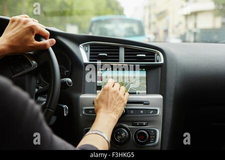 Woman sitting in car, using gps, focus on hands - Stock Image