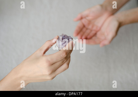 Womans hands giving an amethyst crystal in another womans hands in healing gesture. - Stock Image