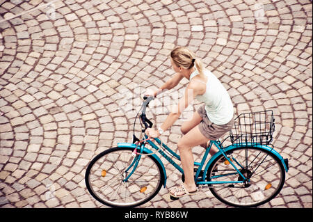 blonde young woman riding a blue bicycle in the city street - Stock Image