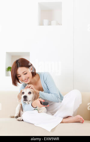 Young woman holding remote control and playing with dog, - Stock Image