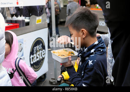 A young Chinese boy eating food from a Borough Market stall in London England UK   KATHY DEWITT - Stock Image