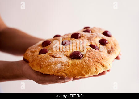 closeup of a young caucasian man with a coca de cireres, a cherry sweet flat cake typical of Catalonia, Spain, typically eaten on Corpus Christi feast - Stock Image