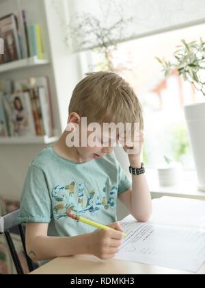 Boy sitting at desk writing - Stock Image