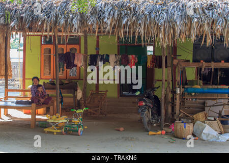 Life in the village: young mother with her son sitting in front of his house - Stock Image