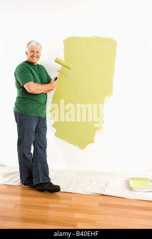 Middle aged man painting wall green with paint roller smiling at viewer - Stock Image