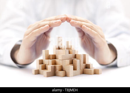 Safety business development concept. Wooden blocks covered by hands. - Stock Image