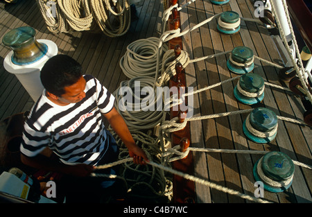 Star Flyer (one of the Star Clippers' ships). A seaman adjusts halyards aboard the Star Flyer, a barquentine - Stock Image