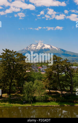 Mount Iwaki on a blue sky day with Hirosaki Park trees and lake in the foreground. In Hirosaki, Aomori Prefecture, Japan. - Stock Image