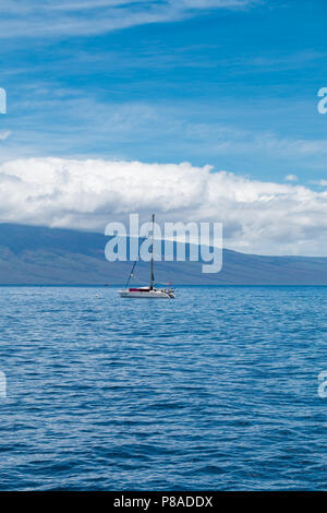 The catamaran, Van Kedisi, anchored on the west coast of Maui with Lana'i in the background. - Stock Image