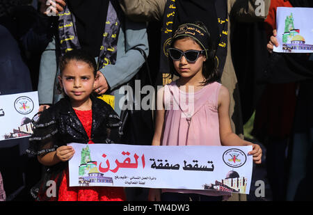 Palestinian girls hold a banner reading 'Down at the Bahrain Conference' during a protest at the Bahrain Peace Plan workshop in southern Gaza Strip. - Stock Image