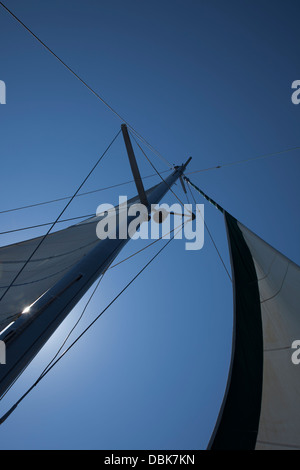 Looking up at a Catamaran mast against a deep blue summer sky. - Stock Image
