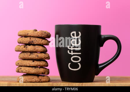 coffee and cookies, mug of coffee with a stack of chocolate chip cookies - Stock Image
