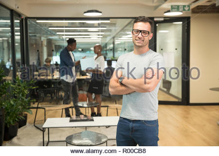 Smiling young businessman in office - Stock Image