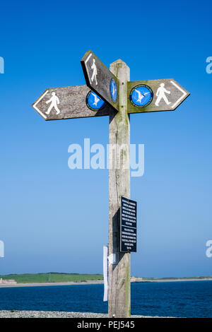 Anglesey Coastal Footpath wooden signpost pointing three directions at Cemlyn Bay, Cemaes, Isle of Anglesey, Wales, UK, Britain - Stock Image
