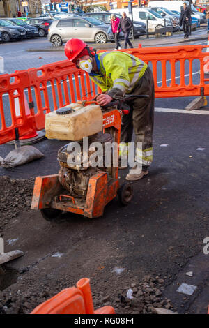 Workmen using a powered saw to make a trench in the road for an electrical power cable - Stock Image