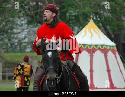Squire in red riding black horse - Stock Image