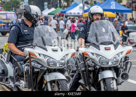 Two Glendale California Police Department motorcycle officers standing by at a public event. - Stock Image