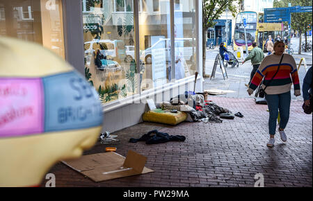 Brighton UK 11th October 2018 - Homeless person on the streets of Brighton beside a Snailspace sculpture - Stock Image
