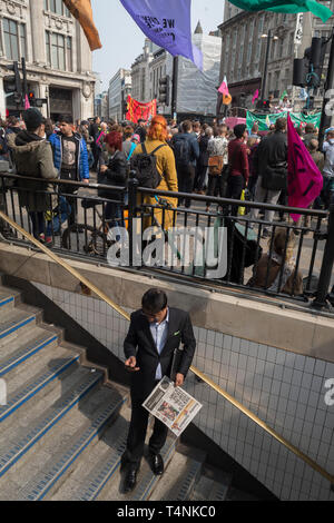 As activists with Extinction Rebellion protest about climate change in a blocked-off Oxford Circus, commuters descend the steps into the underground, on 17th April 2019, in London, England. - Stock Image