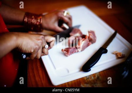 Punjabi woman wearing bangles and jewellery cuts meat with knife. - Stock Image