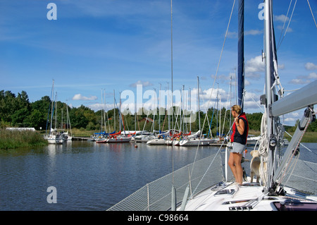 Woman and dog on a sailboat approaching pier, on lake Mälaren, in Sweden, on a summer day. - Stock Image