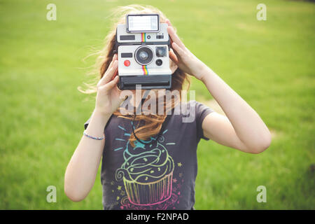 Caucasian girl taking instant photograph outdoors - Stock Image