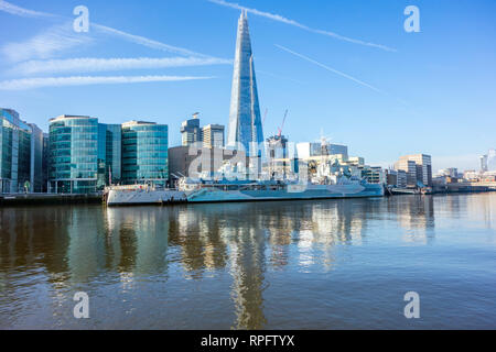 The battleship HMS Belfast moored on the river Thames at Southwark London with the Shard building  in the background on the London skyline - Stock Image