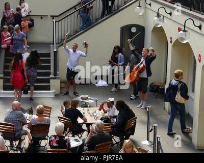Diners listen to a string trio in Covent Garden, London, England - Stock Image