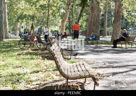 People enjoying and relaxing on a Sunday morning in the sun at the park. Piacenza, Italy. - Stock Image