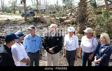 Panama City, Florida, USA. 15th Oct 2018. U.S President Donald Trump speaks to a resident during a tour of damage in the aftermath of Hurricane Michael October 15, 2018 in Lynn Haven, Florida. Standing with the president from left to right are: FEMA Administrator Brock Long, local resident, Florida Gov. Rick Scott, President Donald Trump, First Lady Melania Trump, First Lady of Florida Ann Scott and Homeland Security Secretary Kirstjen Nielsen. Credit: Planetpix/Alamy Live News - Stock Image