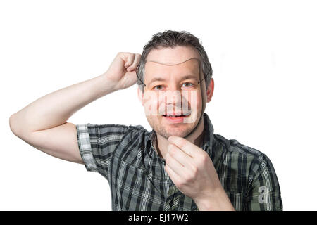 Picture of a man putting on a mask of himself. - Stock Image