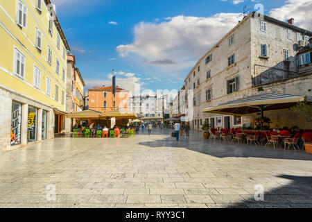 Tourists sightsee and dine at outdoor cafes at People's Square inside Diocletian's Palace in the old town center of Split Croatia. - Stock Image
