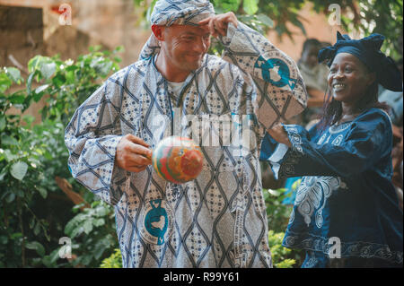 Mature caucasian man singing and dancing. Multi Ethnic music party to celebrate western and developing countries cooperation. Bamako, Mali. Africa - Stock Image