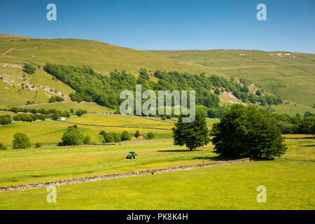 UK, Yorkshire, Wharfedale, Hubberholme, agriculture, farmer mowing hay meadow in sunny summer weather - Stock Image