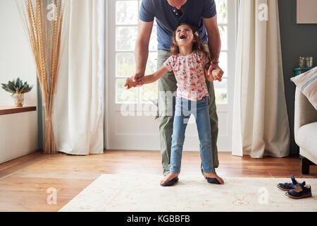 Girl balancing on father's feet at home, looking up - Stock Image