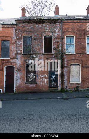 Derelict house boarded up with steel plates, written over with graffiti. - Stock Image