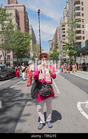 A man at the front of the Hare Krishna Ratha Yatra parade in NYC both takes a selfie & photographs the parade with a go pro camera pointed backwards. - Stock Image