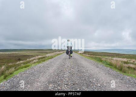 Female cyclist traveling across Northumberland moorland on the UK Coast to Coast cycle route - Stock Image