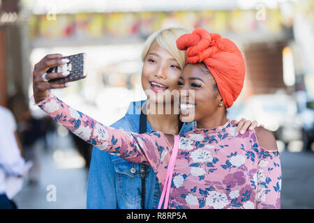 Happy young women taking selfie with camera phone - Stock Image