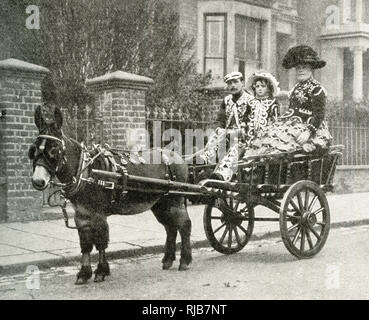 Pearly King, Pearly Queen and daughter, riding in a cart drawn by a mule, North London. - Stock Image