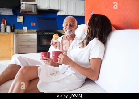 Couple in white bathrobes enjoying mini breakfast with coffee mugs and baking goods in their apartment - Stock Image