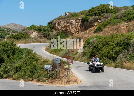 Crete, Greece. June 2019. Couple riding a quad bike on a country lane at Rodopos near Kissamos, eastern Crete, - Stock Image