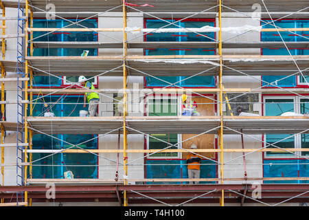 ASHEVILLE, NC, USA-4/11/19:  Workers on scaffolding on the outside of the Arras Building, on Broadway Avenue, near Pack Square. - Stock Image