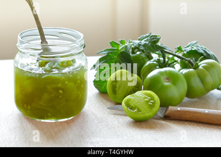Green tomato jam or chutney in a glass jar with vintage spoon, home canning concept - Stock Image