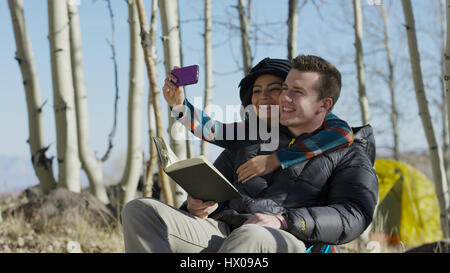 Low angle view of smiling couple hugging and posing for smartphone selfie in autumn woods - Stock Image