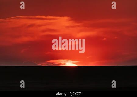 The Sun Breaks the Horizon with Blazing Orange Sky - Stock Image