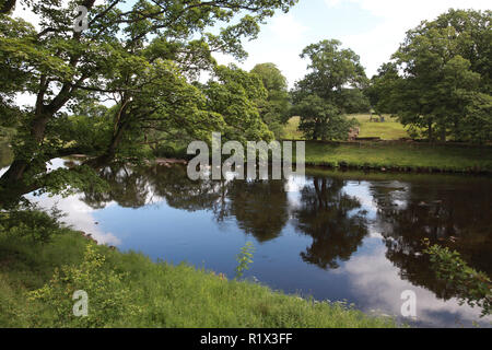 A view across the river North Tyne to the remains of the eastern Chesters Roman Bridge abutment - Stock Image