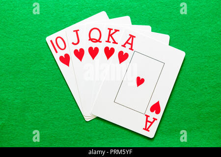 Royal Flush Hearts, a winning hand in a game of poker. Playing cards on a green baize table. - Stock Image
