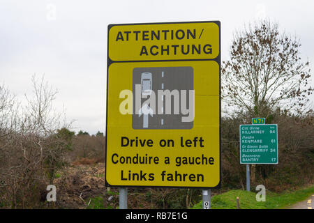 Traffic warning sign to drive on left side of the road. Ireland. - Stock Image